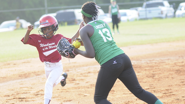 Woodmen of the World's Daysha Smith collides with Interlink Drugs's Mikiha Lindsey on a play at third base Tuesday night during the first round of the 9 and 10-year-old softball playoffs at the Dallas County Sportsplex. Woodmen of the World held on for a 5-2 victory.--Daniel Evans