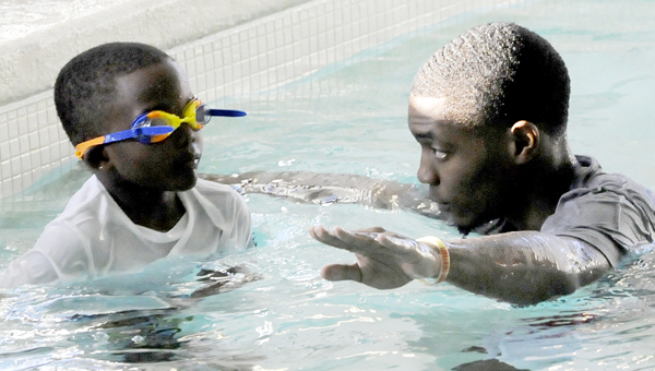 A swimming instructor helps a student during a swim lesson at the YMCA of Selma-Dallas County earlier this year.  In an effort to cut the national drowning rate by 50 percent, the American Red Cross launched a campaign to improve water safety education.