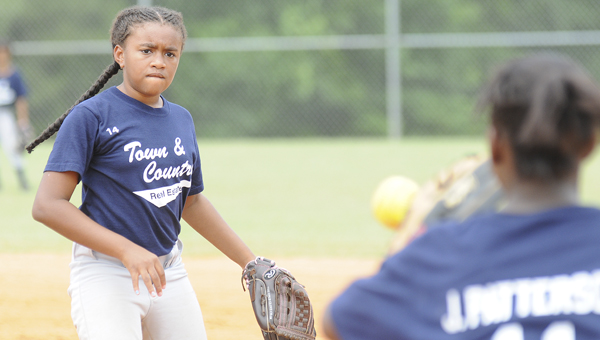 Town & Country's Kaylin Stanberry fields a ground ball and throws to first baseman Jakalyn Patterson during Saturday's game versus Pilcher McBryde at the Dallas County Sportsplex. Stanberry and Town & Country won the game 7-2, forcing a winner-take-all championship game Monday night where the winner will be crowned the 9 and 10-year-old softball championships. --Daniel Evans