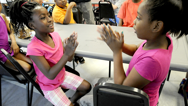 Jordan Weatherly, left, and Makenzi Woods, right, play a hand-clapping game together after lunch while waiting to go do their next activities during the YMCA's Summer Adventure Camp. (Scottie Brown   Times-Journal)
