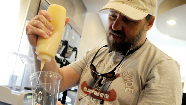 Administrative Pastor Mark Andrews drizzles caramel to make a caramel macchiato at the new Crosspoint Church coffee shop. (Christopher Edmunds | Times-Journal)