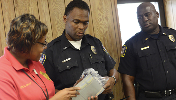 Selma police Sgt. Evelyn Ghant, officer Harry Tubbs and Lt. Curtis Muhannad look over an Award of Merit from the National Water Safety Congress following a presentation Wednesday afternoon in Selma. -- Jay Sowers