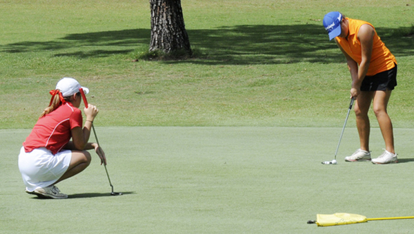 Sarah Battye, left, watches Ashton Maddaloni, right, get ready to take her swing on hole seven during the first round of 53rd Bud Burns Dixie Junior Golf tournament at the Selma Country Club.