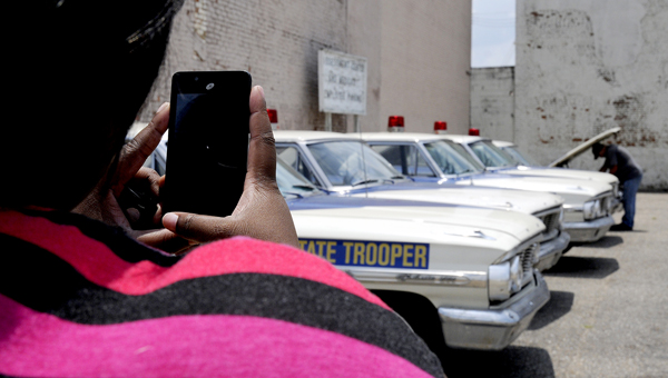 Pebble Davis, a Selma resident, takes a picture of several of the vintage State Trooper cars brought in for the production of the movie 'Selma,' Wednesday afternoon.
