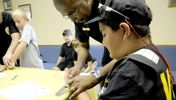 Ross Jones has his fingerprints taken by Chief of Police William Riley during Sister Springs Baptist Church's Agency D3 Vacation Bible School Thursday afternoon. (Scottie Brown | Times-Journal)