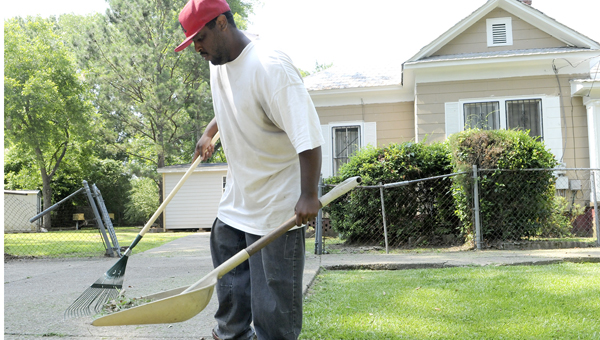Antonio Winston, 31, rakes clippings as his coworkers cut and trim the lawn of a client.