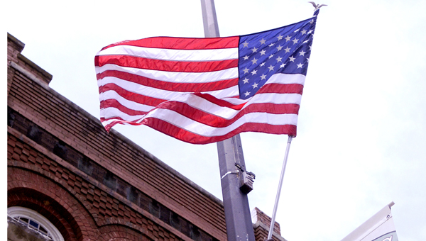 Ledell Tanner, a public works employee, mounts an American flag to a lamppost on Broad Street in preparation for Flag Day.