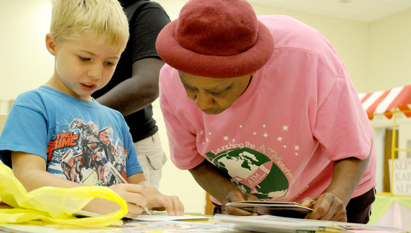Bernice Campbell, right, a member of the Zeta Eta Omega Chapter of Alpha Kappa Alpha Sorority Inc., helps Bradley Freeman, left, 5, pick out a book at the Reading is Fundamental program Monday at the Selma Convention Center.