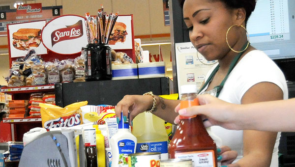 A Dave's Market cashier checks out a customer Monday. The grocery store is part of a complex that's seen increased business in recent years. (Josh Bergeron | Times-Journal)