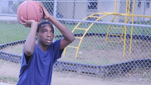 Amos King shoots the basketball Tuesday afternoon on a court along the railroad tracks on Laspley Street.--Daniel Evans