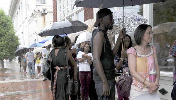 Those interested in being chosen as extras in the upcoming filming of the moving 'Selma' wait just outside the Performing Arts Center Tuesday.  The rain did not stop more than 500 from turning out for the casting call. -- Scottie Brown