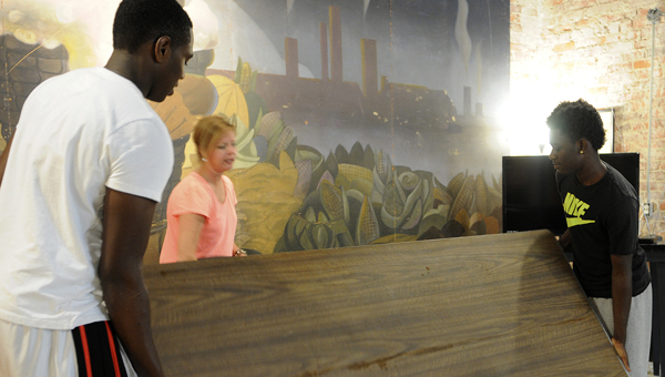 Beth Spivey, center, shows Donnell Bowie, right, and Jacquez Fields, left, how much work they've been able to accomplish while working at the Old Depot Musuem. -- Scottie Brown