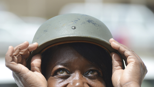 Bettie Pritchett, secretary for the Selma Police Department's Traffic Division, wears a helmet and looks skyward while posing for a photograph Thursday afternoon. Selma Chief of Police William Riley said his department is trying to educate the public about the dangers of firing weapons into the air on holiday like the Fourth of July and New Years Eve. (Jay Sowers   Times-Journal)