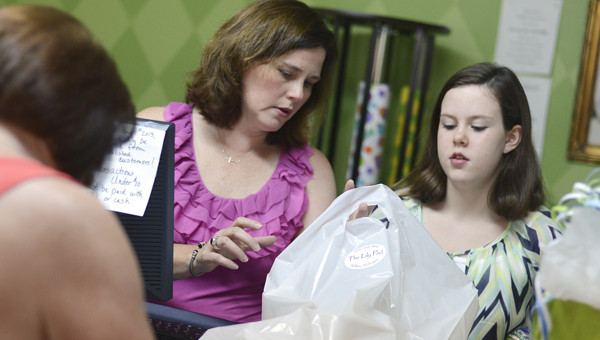 Sherie Leigh Ousley, center, helps her daughter Mary Alan place items in a bag for a customer Friday afternoon at The Lily Pad store in downtown Selma. (Jay Sowers | Times-Journal)