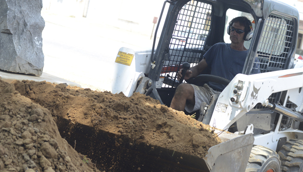 Selma City Councilman Greg Bjelke uses a piece of construction equipment to move piles of dirt at Bienville Park early Monday afternoon.