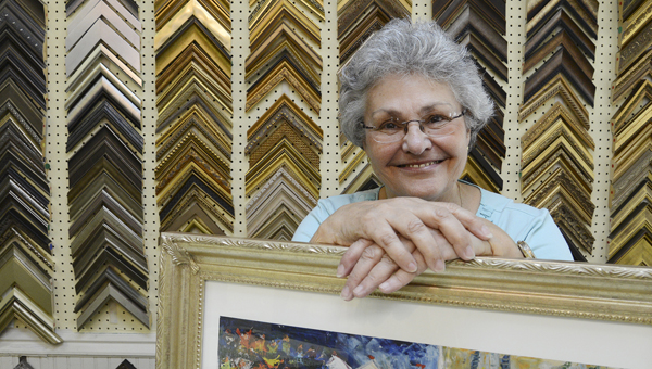 Kay Traylor stands in front of a display of hundreds of frame options Thursday at Frames N' Things, the custom framing store she has owned for 26 years.