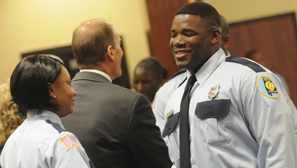 Charlie Long, right, with the Alabama Department of Corrections Class of 2014-02, shakes hands with deparment represenatives Wednesday during the ADOC graduation ceremony held at the Alabama Criminal Justice Training Center. Seventy-two trainees graduated, bringing them one step closer to becoming certified state peace officers.