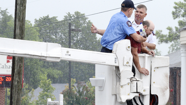 Selma Fire Chief Mike Stokes, center, talks with a first reponder after the two pulled a man from a safety harness that was hanging under a digital billboard on Citizens Parkway Monday morning. Stokes said the man had slipped from a walkway on the billboard and was unresponsive when rescue personnel arrived at the scene. Stokes said the man was unresponsive because his harness had limited his ability to breath for a short period. (Jay Sowers | Times-Journal)