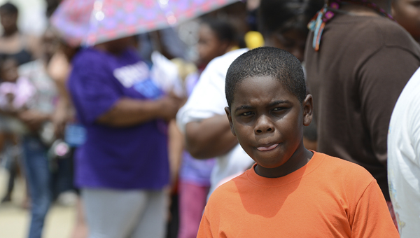 Hundreds of parents and children waited in line to receive free food and school supplies during the 'Slice of Hope' event Tuesday evening at the Edmundite Missions food kitchen in Selma. (Jay Sowers | Times-Journal)