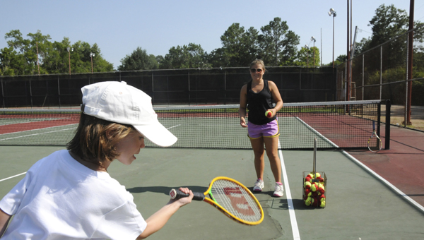 Emily Sherrer tosses a tennis ball to Callie Calame during their practice Wednesday afternoon. Sherrer has been teaching tennis lessons to six and seven-year-olds every Wednesday over the summer. (Scottie Brown | times-Journal)