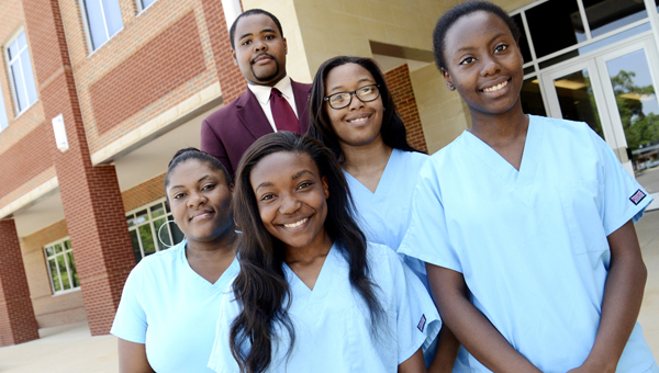 Selma High School Principal Aubrey Larkin Jr., back row, poses for a photo with Selma High School teacher Courtney Carter-Clark , far left, and her Nursing Aide Training class.  Left to right, Yashmin Woods, Mariya Jones and Clydeshia Lewis were students in the class. Brenisha Sims, another student, is not pictured.--Jay Sowers