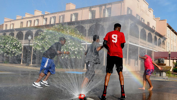 With the historic St. James Hotel in the background, children play in the sprinkler to beat the heat during the recent Jazz on the Grazz in downtown Selma.  Strand Management took control of the iconic hotel Tuesday, taking over the operation from the city of Selma. (Christopher Edmunds | Times-Journal)