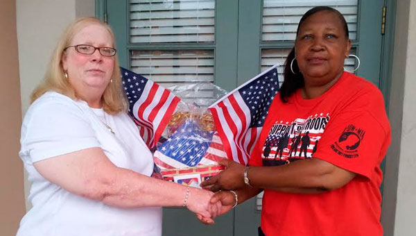 Rae Roth, left, the president of Historic Estates, Landmarks and Properties Inc., hands Selma resident Liz Smiley, right, the gift basket she won in the organization's raffle, which was meant to raise funds for the organization. (Sarah Robinson   Times-Journal)