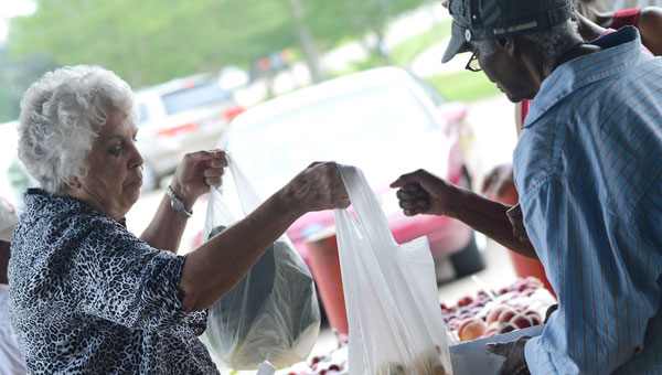 Margaret Harrison, left, hands two bags of fresh produce to a customer in early June at the Selma Farmers Market. (File Photo   Times-Journal)