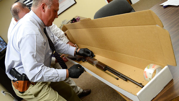 Sgt. Mike Granthum, with the Dallas County Sheriff's Department, secures a .22 caliber rifle in an evidence box Tuesday morning at the department's office in Selma. Authorities believe this is the gun Dallas County resident Eddie Mixon used to shoot and kill his brother, Stanley Mixon, following an argument Monday evening. (Jay Sowers | Times-Journal)