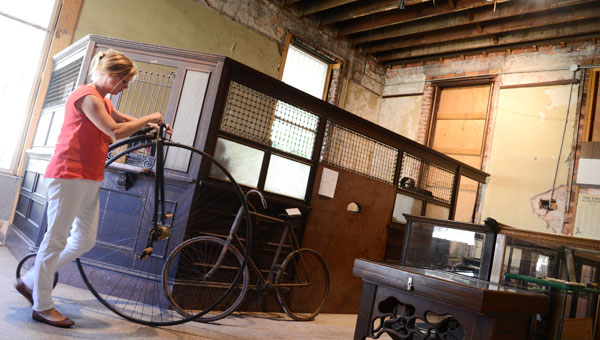 Old Depot Museum director Beth Spivey moves a historic bicycle through a room at the museum Monday morning. (Jay Sowers | Times-Journal)