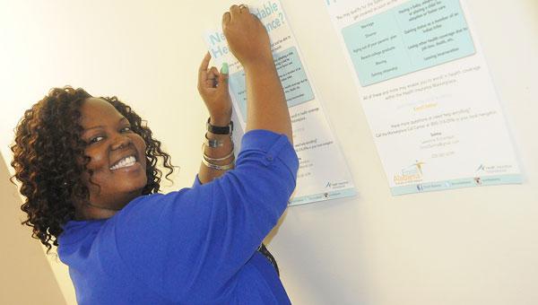 Lawanda Richardson, Selma Field Navigator for Enroll Alabama, hangs up healthcare posters around her office Thursday afternoon. (Daniel Evans   Times-Journal)