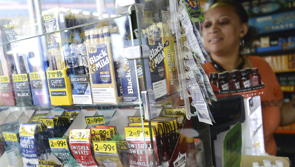 Kesa Williams stocks a shelf with tobacco products Wednesday afternoon at the Cougar Minit Shop in Selma. (Jay Sowers | Times-Journal)