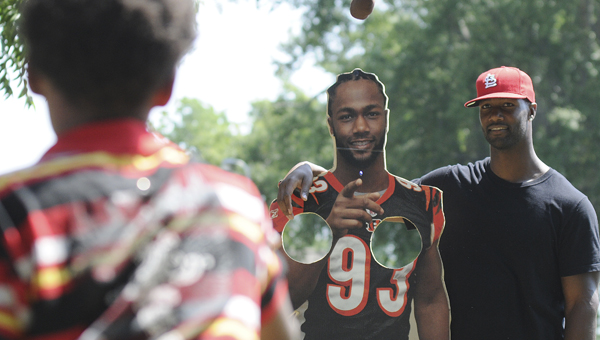 Selma native and NFL star Michael Johnson stands by a cutout of himself donning a Cincinnati Bengals jersey as a participant throws beanbags during Saturday's MJ93 Fun Fest at Concordia College Alabama. Johnson will be a member of the Tampa Bay Buccaneers this upcoming season.