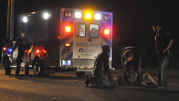 Emergency personnel help a man into an ambulance after he was struck by a car on Dallas Avenue. (Josh Bergeron | Times-Journal)