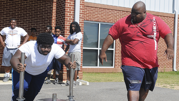 Selma High School student Jermaine Sanders, left, pushes weight on a sled outside the school's weight room Wednesday as Saints' wrestling coach Robert Wilkerson, right, looks on.  Selma will have a wrestling team for the first time this upcoming season.--Daniel Evans