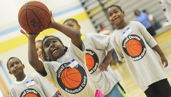 Liyah Herring, one of the campers at Sarrell Dental's Basketball Camp Saturday at Selma High School, smiles as she gets ready to try to shoot the ball. Herring was among the 200 children that took part in the camp Saturday.--Daniel Evans