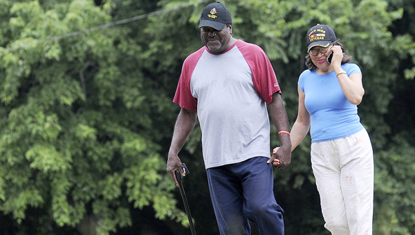 Nathaniel Holmes Jr., left, and his wife Ernestine Marie Holmes, right, were at Bloch Park's walking trail early Friday morning in an attempt to beat the incoming rain. -- Daniel Evans