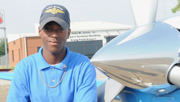 Selma Air Employee and Selma High student Desmond McWilliams stands next to a plane Thursday at Craig Field Airport. McWilliams currently has his student pilot's license but is studying to get his full license (Josh Bergeron | Times-Journal)