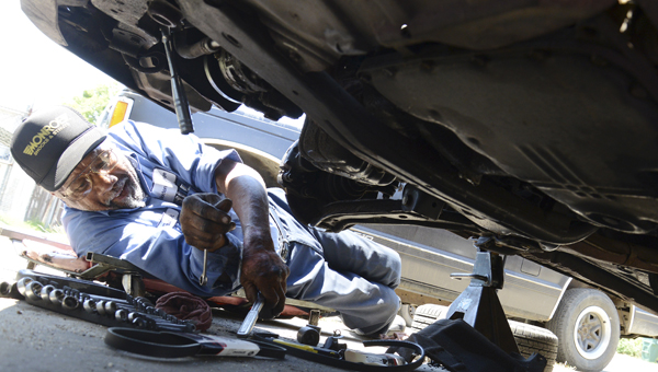 Frank Blocton searches reaches for a socket wrench while replacing two belts on a car at his Selma Avenue garage early Friday afternoon. (Jay Sowers | Times-Journal)