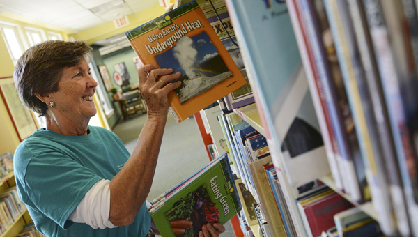 Becky Nichols, executive director of the Selma-Dallas County Public Library, places books back on a shelf Tuesday afternoon in the library's children's section. -- Jay Sowers