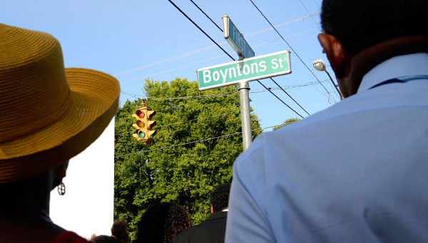 Above, elected officials and community members look up at the new sign for Boyntons Street during a ceremony Saturday afternoon. Below, the event feature songs, powems and speeches.--Jay Sowers