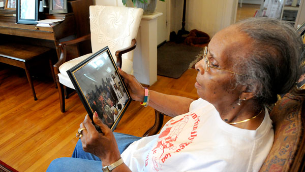 Crandell Brown views a framed photo from a family reunion, where serveal of her children, grandchildren, and great grandchildren were present. Brown said her family photos evoke sweet memories that make her appreciate how far her children have come. (Sarah Robinson | Times-Journal)