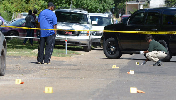 Police investigators look over more than a dozen bullet casings after a shooting occurred Tuesday afternoon on the 1500 block of Philpot Avenue. (Jay Sowers | Times-Journal)