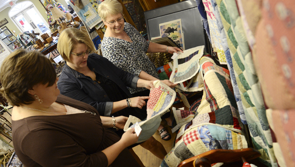 Jennifer Smith, Kristin Law and Sulynn Creswell look over quilts made by local artists at the Blackbelt Treasures Cultural Arts Center in Camden earlier this summer.