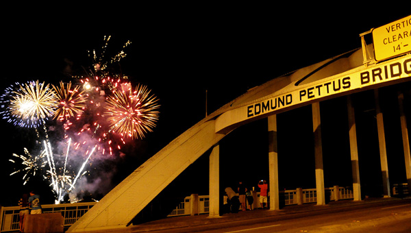 Fireworks explode in the background as spectators line the sidewalks along with Edmund Pettus Bridge last September.  Fireworks will again explode over the Alabama River on Labor Day night. (File Photo |Times-Journal)