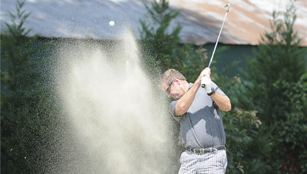 Keith Bradford hits from a bunker adjacent to the ninth green during the first round of the Selma Country Club Championship. Bradford shot a net score of 76 and is ten shots behind leader Jim Mason. --Daniel Evans