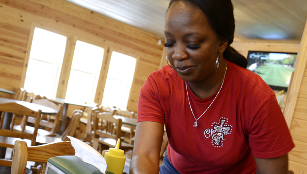 Brenda Purifoy wipes down a table at the Sandbar restaurant Friday afternoon. The restaurant is scheduled to reopen for business at 11 a.m. Saturday morning after being closed for a week-and-a-half due to flood damage. (File Photo | Times-Journal)