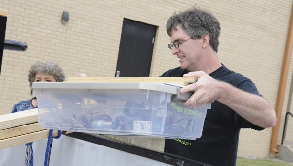 Morgan Academy parent Steve Scheer loads a box full of material given during Saturday's kickoff for the Selma Boosting Engineering Science and Technology Robotics Competition.