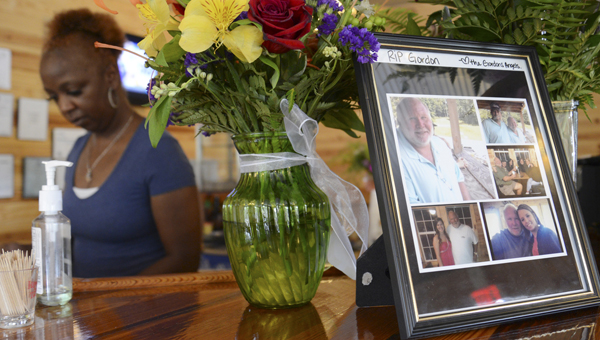 Brenda Haywood works behind the counter at the Sand Bar restaurant Wednesday afternoon near flowers and photos of Gordon McLendon. (Jay Sowers | Times-Journal)