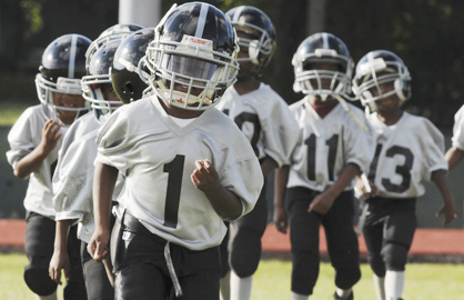 Jordan Lamar leads the Jr. Raiders onto the field as they get introduced Saturday at Memorial Stadium on youth opening day. --Daniel Evans